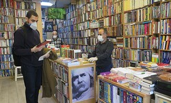 A customer (L) and booksellers are seen at a shop in Tehran on April 18, 2020 after the reopening of the bookstores across Iran after a nearly two-month shutdown due to the new coronavirus pandemic. (