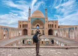 A man takes photos of the historical Agha Bozorg Mosque in Kashan, central Iran.