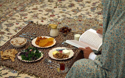 File photo depicts a woman reading verses of the holy Quran beside an Iftar spread in the lunar month of Ramadan.
