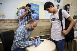 """Writer Mohammad Sarshar autographs a copy of his novel """"Monster Hunt"""" for a reader during the unveiling ceremony of the book at Patoqe Ketab in Tehran on May 30, 2020. (Mehr/Shahab Qayyumi)"""