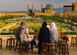 Travelers sit overlooking the UNESCO-registered Imam Square in Isfahan, central Iran.