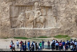 File photo depicts people visiting a magnificent Sassanid-era bas-relief in Naqsh-e Rustam, an ancient necropolis near Persepolis in Fars province, southern Iran.