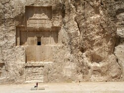 A traveler looks at a massive rock-hewn tomb where a Persian Achaemenid king is laid to rest at the necropolis of Naqsh-e Rostam in southern Iran.