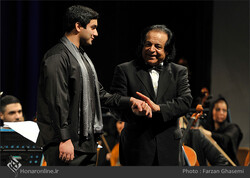 "Maestro Ali Rahbari (R) introduces young composer Puria Khadem to the audience after conducting a performance of his ""Alamdar"" with the Tehran Symphonic Orchestra at Vahdat Hall in Tehran on November"