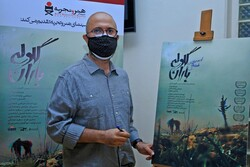"""Co-director Morteza Payeshenas signs a poster for """"The Barrage"""" before a special screening of the documentary at the Iranian Artists Forum in Tehran on September 29, 2020. (DEFC)"""