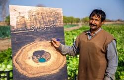 "A farmer signs a poster for Iranian filmmaker Mohsen Khanjahani's latest documentary ""On Soil""."