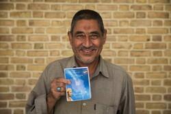 Afghan refugee Abdulrahim Rostami, 66, holds his health insurance booklet in Tehran, Iran.