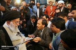 Leader of the Islamic Revolution Ayatollah Seyyed Ali Khamenei glances at a book by Tehran-based Afghan writer Mohammad-Sarvar Rajai (C) during his annual meeting with poets and literati on May 20, 20