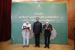 Painter Amir-Hushang Jazizadeh (L) and maestro Taqi Zarrabi (R) pose after accepting their medals from Deputy Culture Minister for Artistic Affairs Seyyed Mojtaba Hosseini (C) at the Girls' Music Acad