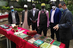 An organizer (R) talks to visitors at a Quran exhibition underway at the culture center of the Embassy of Iran in Kampala, Uganda.