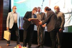 Director Majid Majidi (R) receives the IAA Plaque of Glory from Iranian Academy of Arts director Bahman Namvar-Motlaq in Tehran on July 1, 2021.