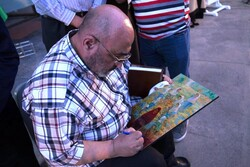 """Abdolhamid Qadirian autographs a copy of his painting """"Girls of the Sayed Al-Shuhada School"""" for a student after unveiling the original the Seyyed al-Shohada Girls' School in Golshahr on July 18, 2021"""