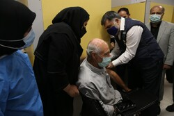 WHO representative to Iran Jaffar Hussain injects a vaccine into a client in a visit to a COVID-19 vaccination center in Tehran on August 25.