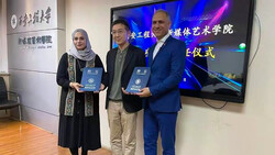 Director Narges Abyar (L) and cultural activist Hossein Khalifi (R) pose with an unidentified person after being decorated with the title of honorary professor of the Xi'an Jiaotong University.